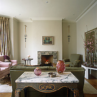 This contemporary living room has a pink and green colour scheme with walls painted in stone