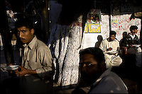 local merchants take a lunch break at a street side vendor's kiosk in the old city of lahore