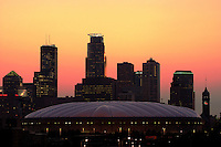 The Metrodome rests in the foreground of the Minneapolis Skyline on a summer evening