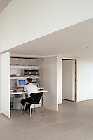 A practical 'home-office' has been built into a cupboard in this minimal loft
