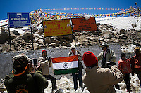 Tourists hold up the national flag of India for photos as they stop on the top of the Khardung La pass at 5602m in the Nubra Valley, Ladakh on 4th June 2009. The valley of Ladakh is located in the Indian Himalayas, in the northern state of Jammu and Kashmir. Photo by Suzanne Lee