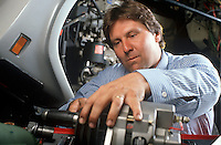 Truck mechanic works on truck part.