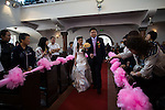 A christian couple marches down the aisle during a mass wedding at the German protestant church in the old town of Qingdao.  The christian community has about 1200 members.