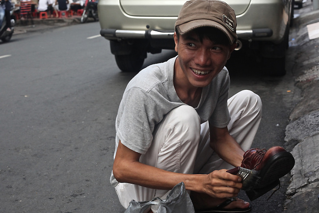 A shoeshine man is at work early on Bui Vien Street in Ho Chi Minh City, Vietnam. Aug. 27, 2011.