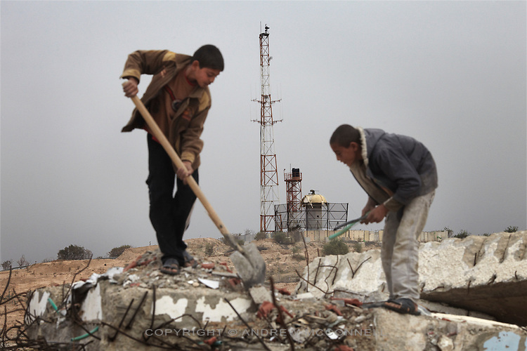 In clear view of an Israeli watchtower Palestinian children collect rubble from the former Israeli settlement of Elei Sinai in Gaza's northern buffer zone. Men and children come here daily to gather building materials even though the area is a no-go zone and dozens have been maimed and killed by Israeli soldiers.