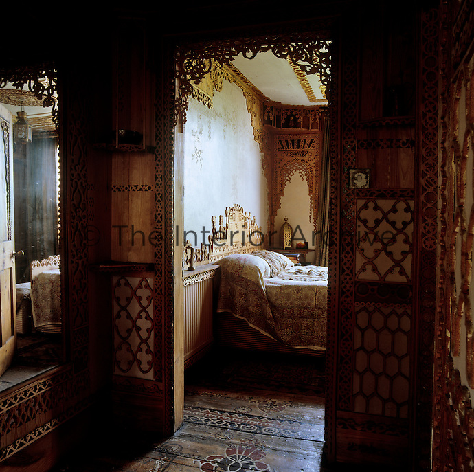 The doorway into the bedroom has been framed with fretwork as have the landing walls and the floorboards have been hand-painted