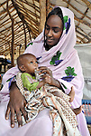 In a primary health care and nutrition center sponsored by ACT-Caritas in Um Labassa, Darfur, a mother gives her malnourished baby Plumpy'Nut, a nutrition supplement.