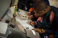 "NEW YORK, NY - MARCH 31: Jazz's singer Cécile McLorin Salvant signs some pieces bought during her expo ""The Adventures of the invisible Woman"" at RAW space on March 31, 2017 in Harlem, New York. Photo by VIEWpress/Eduardo MunozAlvarez"
