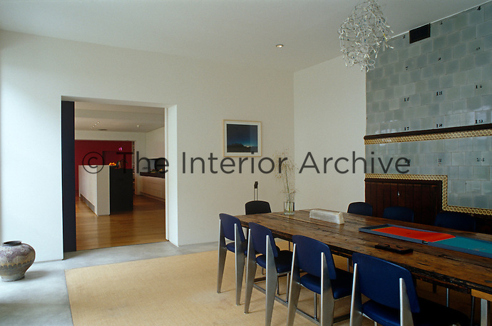 An old wooden table is juxtaposed with a set of modern chairs and this otherwise modern dining room has one wall partly decorated with ceramic tiles