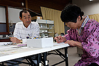 Isao Sanno (left) watches as a farmer fills-in forms at the Becquerel Centre in a farmers' market in Miharu, where locally grown food is tested for nuclear contamination. Miharu, Fukushima, Japan. Friday May 4th 2012