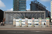 Entrance to the Bahnhof or train station on Potsdamer Platz, with sections of the Berlin Wall covered in graffiti and information panels, Berlin, Germany. The Berlin Wall was constructed in 1961 by East Germany, the former GDR, to surround West Berlin, and was brought down in 1989. Picture by Manuel Cohen