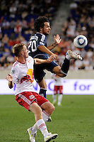 Davide Chiumiento (20) of the Vancouver Whitecaps plays the ball under pressure from Jan Gunnar Solli (8) of the New York Red Bulls. The New York Red Bulls  and the Vancouver Whitecaps played to a 1-1 tie during a Major League Soccer (MLS) match at Red Bull Arena in Harrison, NJ, on September 10, 2011.