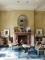 A pair of contemporary Louis XVI style chairs combines with a pair of console tables either side of the fireplace in the living room