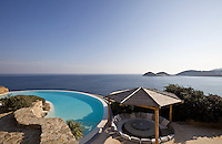 A sunken concrete dining area with a thatched roof next to the infinity pool with a panoramic view of the Aegean sea