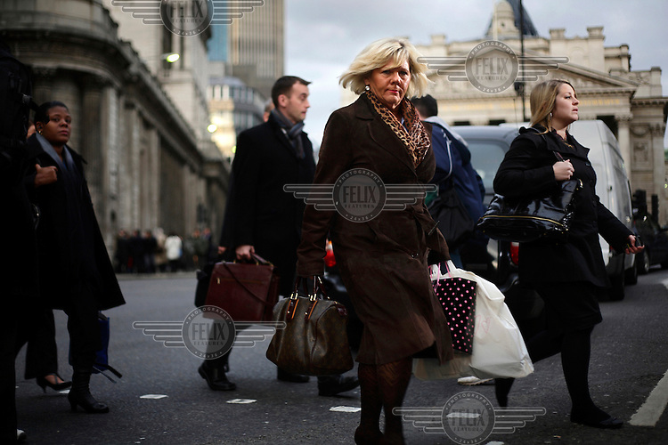 Linda Pitt, who works for Europe Arab Bank in the City of London, crossing the road in the early evening rush hour outside Bank station. The UK went into recession in the final quarter of 2008 as the City was hit hard by the global credit crunch.