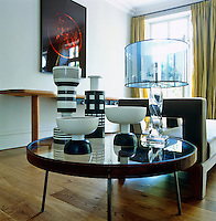 A collection of black and white ceramics by Ettore Sottsass is displayed on a glass-topped table in the living room