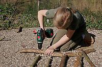 Kinder basteln Klangspiel aus Ästen, Mädchen bohrt mit Akkubohrer ein Loch in den Rahmen-Ast