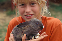 Young girl plays with pet rabbit at family style vacation campground.