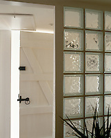 Contemporary glass bricks have been used to create a cloakroom in the entrance hall of a converted schoolhouse and form a pleasing contrast to the original tongue-and-groove oak door