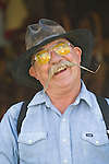 Cowboy Skeeter Clark with mustache, black hat, yellow glasses