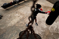 A young Peruvian girl practices with a punching bag at the Boxeo VMT boxing club in an outdoor gym in Lima, Peru, 3 July 2013. Boxeo VMT is a grassroots organisation offering boxing lessons to youth as an alternative to gang violence, crime and drug-trafficking. Located in some of Lima's most marginalized neighborhoods, Boxeo VMT club joins nearly 50 young men. Although the club disposes only of an unequipped outdoor facility with couple of punching bags, the young boxers train hard three times a week and dream to become a boxing champion.