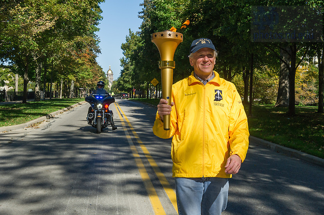 October 8, 2016; University President Rev. John Jenkins, C.S.C., carries the Indiana Bicentennial Torch down Notre Dame Avenue. (Photo by Barbara Johnston/University of Notre Dame)