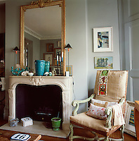 A gilt mirror hangs above the mantelpiece of a traditional fireplace. Next to it stands a wooden chair. The room has many small items of interest placed about it, such as ceramics and paintings