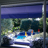 A blue awning extends over a terrace with a view to the outdoor swimming pool below