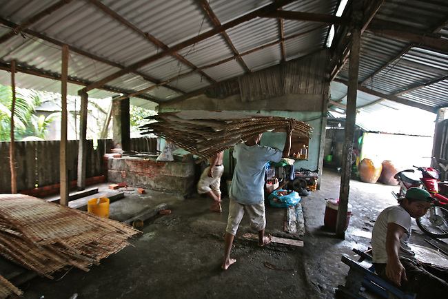 A man carries a stack of freshly made rice noodle sheets outside to dry at a small factory in the Mekong Delta, south of Can Tho, Vietnam. Sept. 30, 2011.