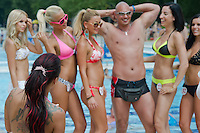 Participants pose with a viewer for photographers during the Miss Bikini Hungary beauty contest held in Budapest, Hungary on August 06, 2011. ATTILA VOLGYI