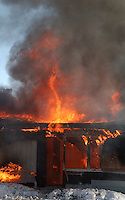 Flame whirls from the collapsed roof of fully engulfed home at the conclusion of a training fire in Alaska.