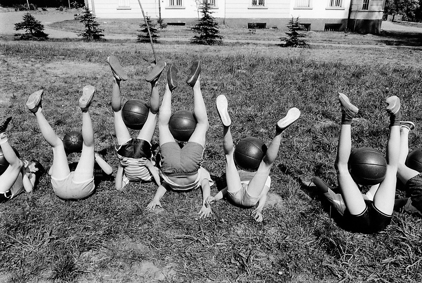 Poland. Silesia. Kameniec. Sanatorium for children, aged 7 to 15 years. A group of boys and girls are laid on their backs and play with a huge ball between their legs. Major polluted area due to heavy metals supended in the air. Kameniec is a small town, distant 35 km from Katowice. © 1991 Didier Ruef