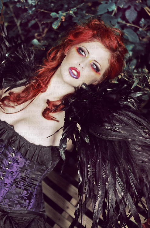 Close-up of a young woman with makeup looking like a vampire with feathers and a corset
