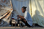 A woman cooks in a camp for homeless families set up on a golf course in Port-au-Prince, Haiti, which was ravaged by a January 12 earthquake.