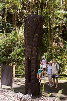 "Tourists read a sign next to a carved wooden tiki (or ki'i in Hawaiian, or statue) of the Hawaiian god ""KU"" at Hawai'i Tropical Botanical Garden, Onomea, Big Island of Hawaiʻi."
