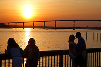 A couple shares an intimate moment at Solomons Island, MD overlooking the Governor Thomas Johnson Bridge on Rt. 4 at sunset. This bridge, connecting Calvert and St. Mary's County, is over 140 feet high with only a jersey wall separating you from the 120 foot deep Patuxant River below.