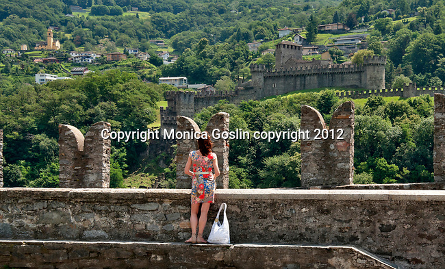 A view of two of three castles in Bellinzona, Switzerland including a view of the Church of Saint Peter in downtown Bellinzona. A woman looks at the view of Bellinzona, Switzerland