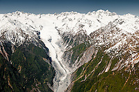 Aerial views of Franz Josef Glacier tongue and its valley. In top right corner - Mt. Tasman 3497m on left and Mt. Cook 3754m right dominate skyline, Westland National Park, West Coast, New Zealand