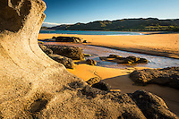 Rock formations on golden beach in Totaranui during sunset, Abel Tasman National Park, Nelson Region, New Zealand