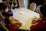 Sophia Sawyer, right, helps her children, from left, Frances, Isaiah, and Daniel, with their homework January 27, 2010 in Sacramento, Calif. The Sawyer family receives $540/month in CalWORKs assistance from the state of California. Dennis is currently unable to work while recovering from cancer, and Sophia hasn't been able to find work. Gov. Arnold Schwarzenegger has proposed eliminating the CalWORKs program in an effort to balance the state's budget. CREDIT: Max Whittaker for The Wall Street Journal.CABUDGET