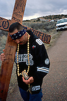 A cross-carrying pilgrim stops to buy a Virgen de Guadalupe rosary enroute to the Santuário de Chimayó in northern New Mexico on Good Friday. Thousands of pilgrims make a pilgrimage to the 190-year-old shrine every Easter as an expression of faith, a connection to old Hispanic roots and in hopes of the miracles reputed to occur there.