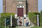 Foto: VidiPhoto<br /> <br /> HOMOET - Een bijzondere burendag in de Betuwse buurtschap Homoet zaterdag. Daar besloten de buren van het monumentale waterschapskerkje, Rob en Jacomien Evers, de roestige poort van het godshuis een schilderbeurt te geven. Het piepkleine hervormde kerkje -en met slechts 50 zitplaatsen een van de kleinste van ons land- is dringend toe aan restauratie. De familie Evers maakte zaterdag vanwege burendag alvast een begin met het hek aan de buitenzijde. Het Rijksmonument dat midden in het open landschap staat en aan het begin van de 19e eeuw diende als 'vluchtheuvel' voor boeren bij hoogwater, is het enig overgebleven waterstaatskerkje in de Over-Betuwe van de oorspronkelijk vijftien vluchtkerkjes.