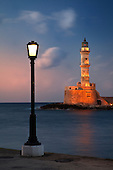 Lighthouse and lighted lamp post at dusk, Chania, Crete, Greece