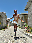 """Cheslin Basin, 8, jumps rope amid houses in a model resettlement village constructed by the Lutheran World Federation in Gressier, Haiti. The settlement houses 150 families who were left homeless by the 2010 earthquake, and represents an intentional effort to """"build back better,"""" creating a sustainable and democratic community."""
