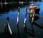 Wooden jetty showing reflections of boat and wooden posts,  Norway.