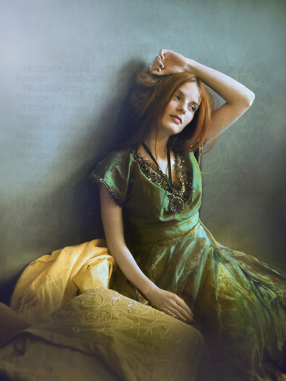 A woman in a green victorian dress, seated by the wall, with her hand stretched above her head, and a thoughtful, dreamy expression.
