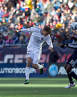 DC United defender Marc Burch (4) heads the ball. In a Major League Soccer (MLS) match, the New England Revolution defeated DC United, 2-1, at Gillette Stadium on March 26, 2011.