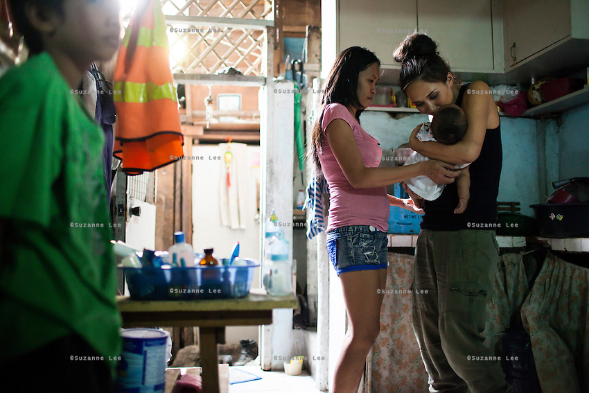 UK celebrity Myleene Klass (in black) meets underprivileged mother Irma Asoro, 29, and her son John Michael (left), 11, as she holds her 4-month-old baby, Rashed James, who she has been feeding formula since he was 2 days old, in her rented home in an urban slum in Paranaque, Metro Manila, The Philippines on 19 January 2013. She thinks that formula is better for her baby even though the cost of formula and bottled water costs her more than double her rent, and she has to borrow from family and friends to pay for it. Photo by Suzanne Lee for Save the Children UK
