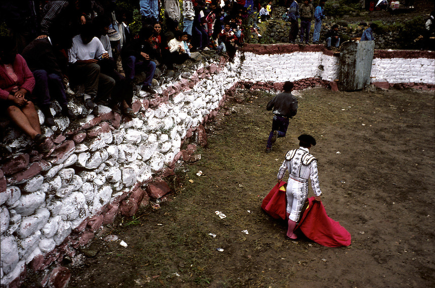 A matador spreads his cape at his feet while a ring attendant scrambles to release a bull at a small bullfight in Ollantaytambo, Perú. Spectators lined the walls of the small ring and watched as their neighbors' bulls — and cows and calves — playfully battled local matadors.
