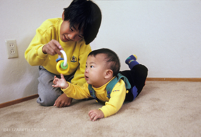 Palo Alto CA Brother ten-years- old entertaining baby broth, eight-months-old with rattle